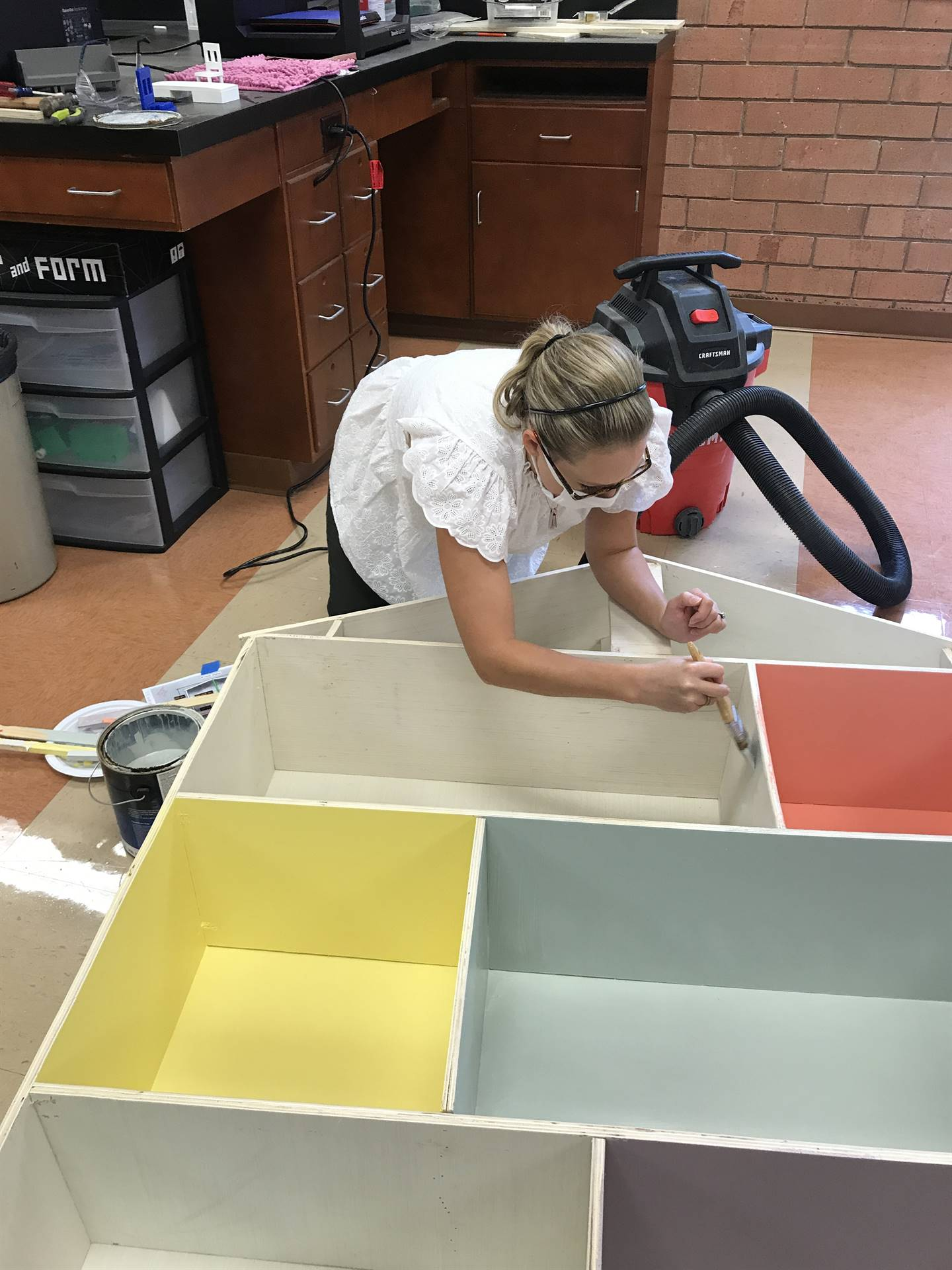 instructor painting doll house