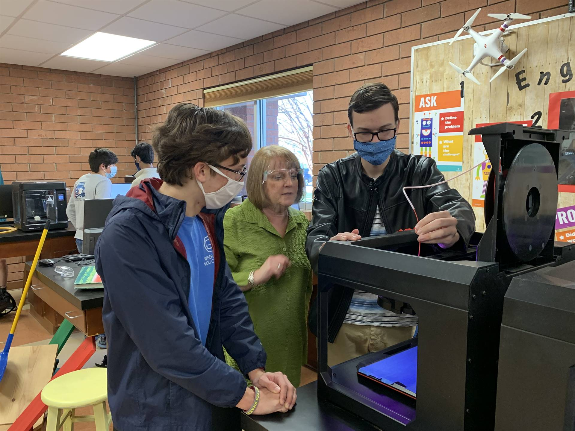 Students and teacher loading 3D printer
