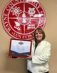 Teacher holding a plaque